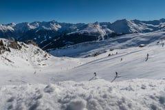Berg och skiiers på en skidasemesterort i vintern arkivfoto