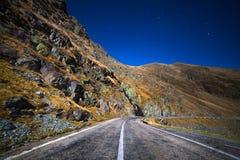 Berg och tom väg på natten Arkivfoton