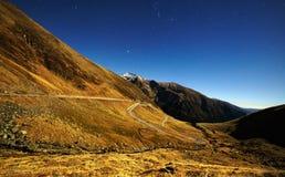 Berg och tom väg på natten Royaltyfri Bild