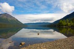 Berg och träd reflekterade i en lugna sjö längs den cassiar huvudvägen fotografering för bildbyråer