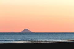 Berg over Gouden Oceaanzonsondergang Stock Afbeelding