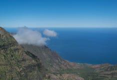 Berg, Ozean und eine Wispy Wolke stockfotos