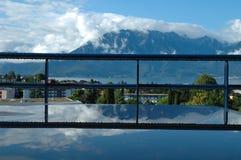 Berg på Geneve sjön reflekterade i vatten på tabellen Arkivbild