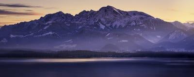 Berg på sjön på solnedgången Royaltyfria Bilder