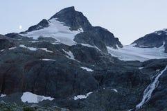 Berg på skymning med halvmånen royaltyfri fotografi