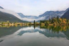 Berg reflekterade i det släta vattnet Arkivfoto