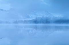 Berg reflekterade i sjön i tät dimma Arkivbild