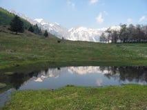 Berg reflektierte sich in einem alpinen See im Frühjahr Lizenzfreie Stockbilder