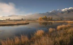 Berg sjö i morgonmisten på bakgrunden av snöig berg och blå himmel royaltyfri fotografi