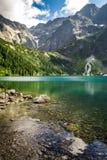 Berg sjö i sommar på bakgrunden av steniga berg Royaltyfri Bild