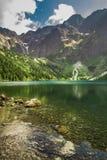 Berg sjö i sommar på bakgrunden av steniga berg Arkivbild