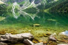 Berg sjö med blått vatten och steniga berg Arkivbild