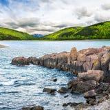 Berg sjö med den steniga kusten på soluppgång Arkivfoto