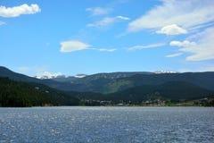 Berg sjö med en stad och en Ski Resort Mountain i avståndet Royaltyfri Fotografi