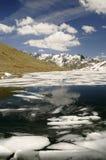 Berg sjö med isisflak i berg Arkivbild