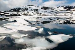 Berg sjö med reflexionen av bergen och isen, Norge Arkivbild