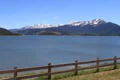 Berg sjö med snö och staketet Arkivfoto