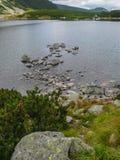 Berg sjö med stenar i vattnet Arkivbild