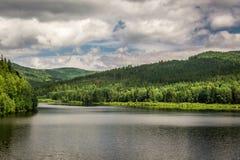 Berg sjö mellan skogar Arkivfoto