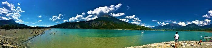 Berg, sjö, moln och stranden arkivfoto
