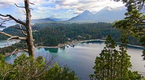 Berg sjö och liten by i skogen royaltyfria bilder