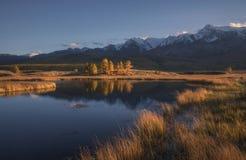 Berg sjö på en bakgrund av höstlandskapet och korkade berg för snö fotografering för bildbyråer