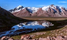 Berg sjö på en bakgrund av hjässorna Arkivfoto