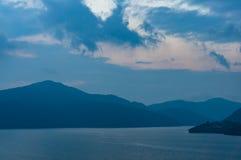 Berg sjö på skymning med bergkonturer i avståndet royaltyfri fotografi