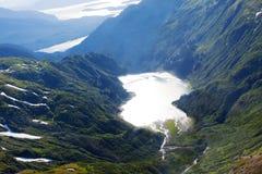 Berg sjö som reflekterar solen Arkivfoto
