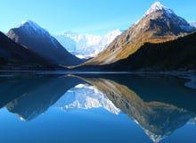 Berg sj?n mellan vaggar med reflexion i vattnet arkivbilder