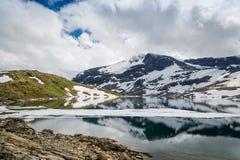 Berg sjön och snöig vaggar, Norge Arkivbilder