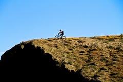 Berg som cyklar nära en klippa Royaltyfria Foton