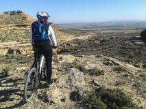 Berg som cyklar ryttaren som ser öknen Royaltyfri Fotografi