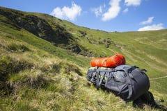 Berg som fotvandrar ryggsäckutrustning på gräset med bergla Royaltyfri Foto