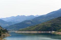 Berg som täckas av pinjeskogar som stiger ned till sjön Royaltyfri Fotografi