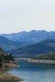Berg som täckas av pinjeskogar som stiger ned till sjön Arkivfoton
