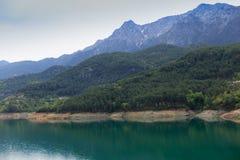 Berg som täckas av pinjeskogar som stiger ned till sjön Arkivfoto