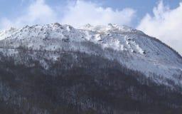Berg som täckas av snöbakgrund i blå himmel i en solskendag Royaltyfri Foto