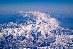 Berg som täckas med snö och moln, flyg- sikt Jordplanetyttersida Resa runt om världen miljö arkivfoto
