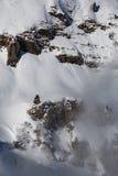Berg som täckas med snö och moln och träd royaltyfri bild