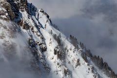 Berg som täckas med snö och moln och träd arkivfoton