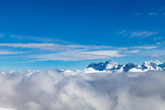 Berg som täckas med snö och omges av moln arkivfoto