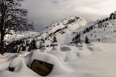 Berg som täckas med snö och omges av moln arkivbilder