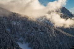 Berg som täckas med snö och omges av moln arkivbild