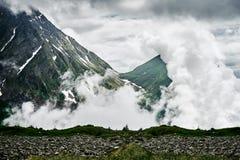 Berg täckas av moln arkivfoto