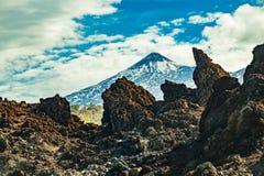 Berg Teide mit den wei?en Schneestellen, teils bedeckt durch die Wolken Heller blauer Himmel Enorme Lavafelsen im Vordergrund Tei lizenzfreies stockfoto