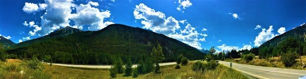 Berg, träd, moln och gatan fotografering för bildbyråer