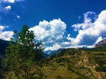 Berg, träd och moln royaltyfria foton