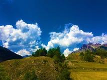 Berg, träd och moln royaltyfri foto