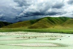 Berg und Fluss unter dunklen Wolken Lizenzfreies Stockbild